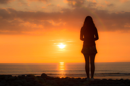 Young woman stands looking out to sea at the sunset Stock Photo