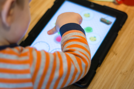 Child using a touch screen tablet to play learning game Stock Photo