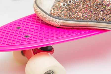 Close up of girls shoe on a pink skateboard Stock Photo