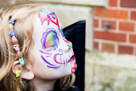 Young girl with beautiful but scary face paint Stock Photo