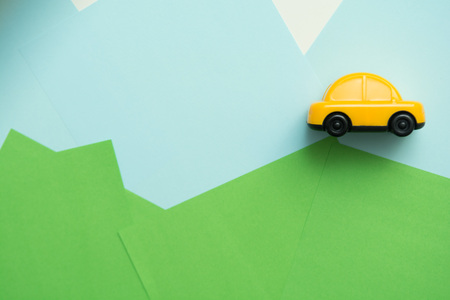 Yellow car driving over hills with blue sky background