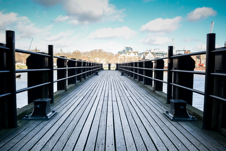 Wooden pier in a peaceful scene overlooking a city river Reklamní fotografie