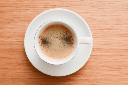 Espresso in a white cup on wooden table