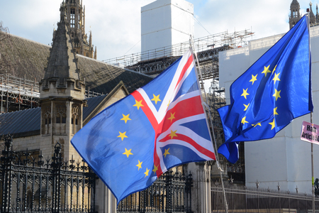 EU and UK flags flying together outside parliament in london