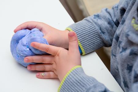 Jouer avec du slime fait maison. L'enfant joue avec la boue faite à partir de la recette