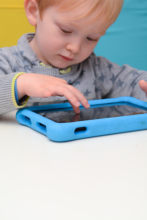 Happy young child is using a tablet computer. Boy is playing with device at home on sofa
