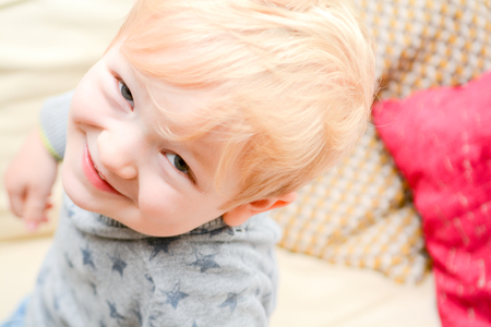 Happy child at home looking directly at camera. Cute blond boy is smiling