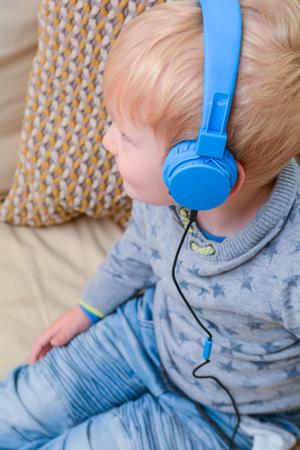 Child enjoying listening to music on headphones Banco de Imagens
