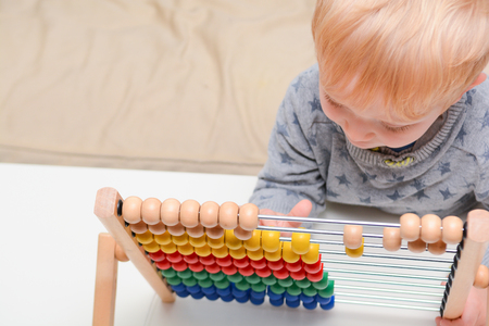 Child learning to count. Young boy using an abacus to learn maths