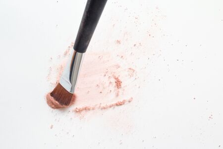 Make up brush on white surface, cosmetic makeup powder exploding as it impacts table