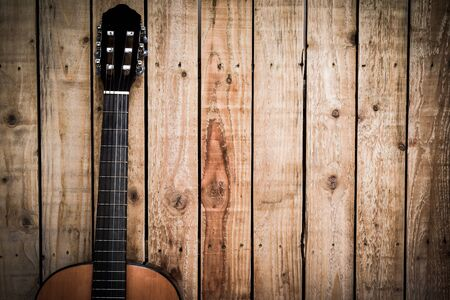 Acoustic guitar on vintage style wood background. Copy space with musical guitar instrument 免版税图像