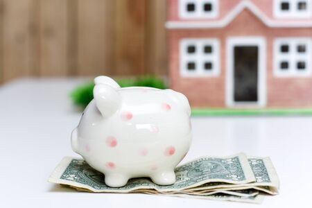 Piggy bank and new home, concept of saving money to pay for mortgage of new property