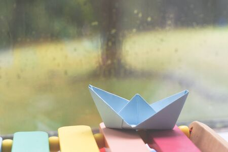 Origami boat by a window on a rainy day inside the house Imagens