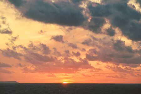 Dramatic sky with orange sunset over the ocean Coastal landscape scene over the water