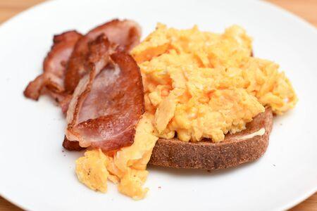 Speck und Rührei mit Toastscheibe auf einem weißen Teller Standard-Bild