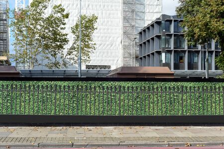 Fake hedge hoarding protects public from works at the construction site and building works