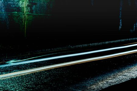 Light trails from cars passing through a dark tunnel on a rainy night