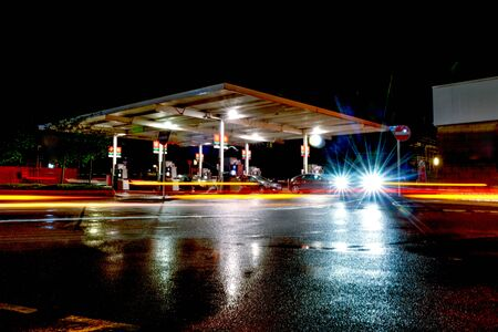 Gas station at night with lights from passing cars as people fill up with petrol