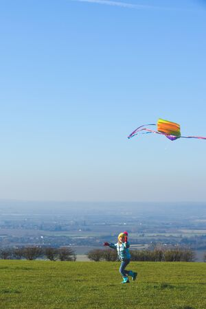 Child flying a kite outdoors on a sunny clear day in a country field