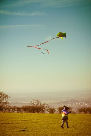 Boy playing outside with a kite, running outdoors during the day with retro style filter