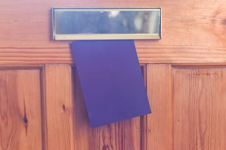 Blank leaflet or flyer being posted through a letter box unwanted junk mail