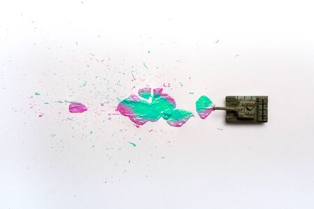 A toy tank shoots out bright coloured paint instead of bullets and shells Фото со стока