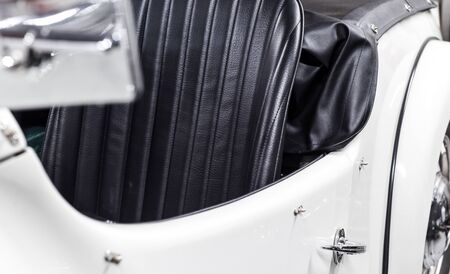 Restored classic car in white with black leather interior and chrome detail