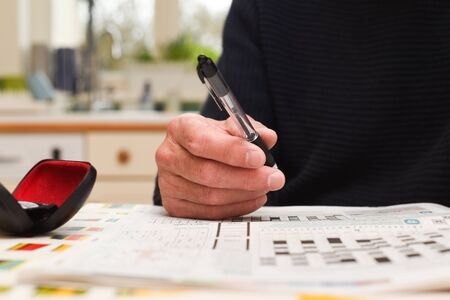Mature man doing a crossword puzzle and relaxing at home during the day, indoor shot