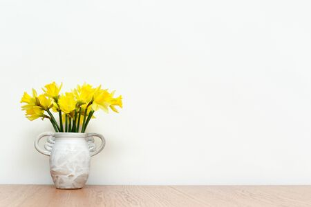 Flowers in a rustic style vase on wooden table with white interior wall background, daffodils