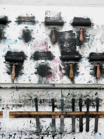Printmaking rollers hanging on an art studio wall in the messy workshop