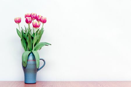 Pink tulips flowers in a vase on wooden table with white interior wall background