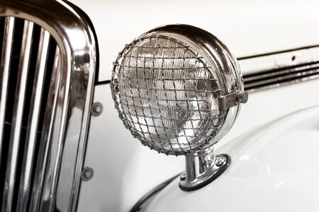 Classic white car in front view with detail on vintage style headlamp