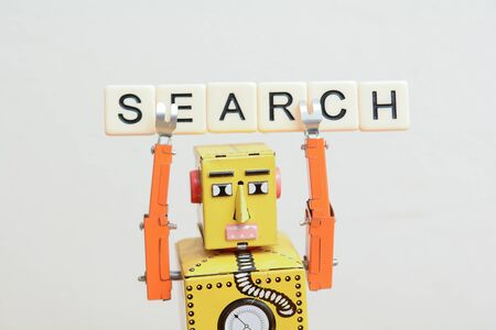 Search engine robot is looking for the best online website metaphor with toy robot on computer curuit board