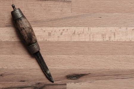 Old knife with wooden handle with dark colours and shadow on a table