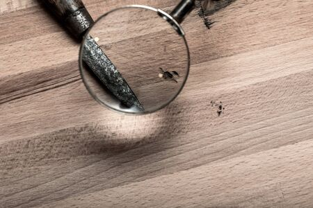 Looking through a magnifying glass at a knife for crime scene clues Фото со стока