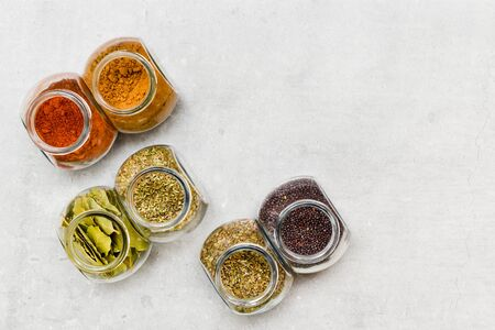 A selection of herbs and spices for adding flavour to food when  cooking on a kitchen worktop at high angle