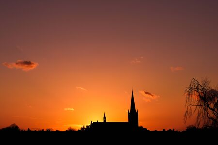 Church building exterior in silhouette of sunrise or sunset with glowing sunlight Stock Photo
