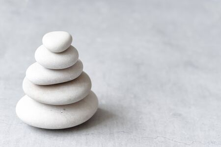 Stack of white pebbles on a neutral light grey background as balance and wellness concept
