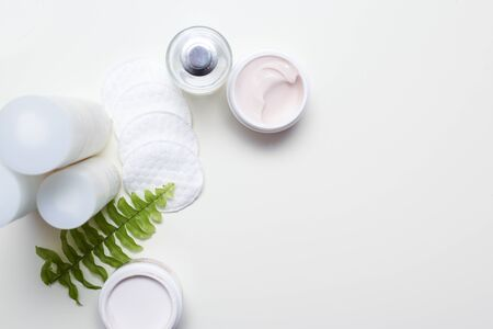 Facial cleansing products and containers with face creams and cotton wool pads Фото со стока