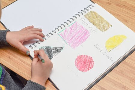 Child learning at home. Pre school age child learning about shapes and hand writing