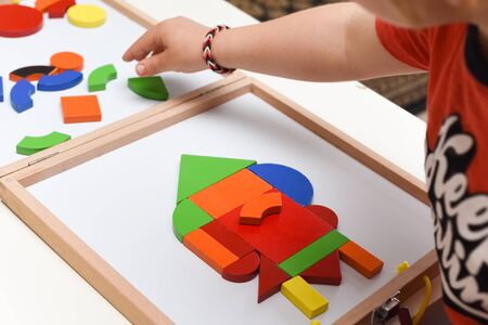 Child playing with colourful puzzle toy making shapes to learn at home