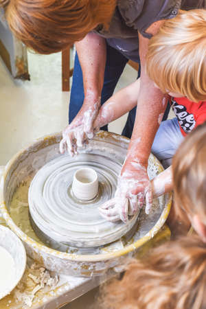 Children learning to make pottery as a hobby with their grandmother in a ceramics workshop Фото со стока