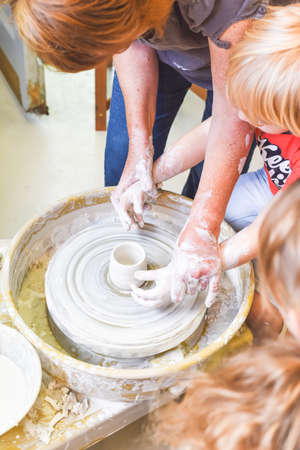 Children learning to make pottery as a hobby with their grandmother in a ceramics workshop Stock Photo
