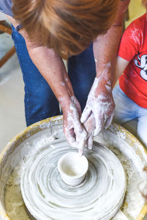 Children making pottery during ceramic lesson with clay