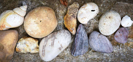 Banner of natural rocks and pebbles arranged on granite surface
