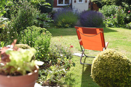 Relaxing area in garden with a deck chair on the lawn during a sunny day 免版税图像