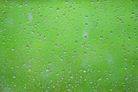 Water drops dripping on glass of window after rain Фото со стока