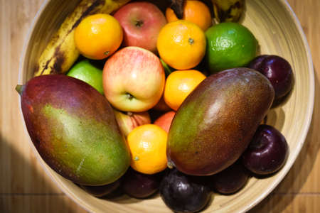 Healthy selection of fruit in a bowl on a kitchen table Stock Photo