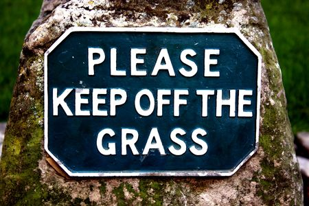 literal: Please keep off the grass sign on a moss covered stone. Either literal or drugs metaphor. Stock Photo