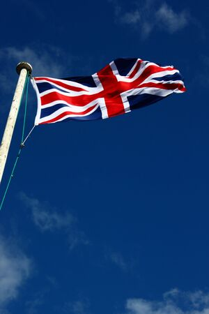 Union Flag on a windy day. This is the flag, generally regarded, to represent the peoples of England, Scotland, Wales and Northern Ireland. The image may show the effect of the wind at full size. Stock Photo